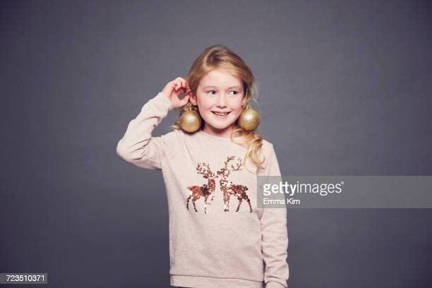 Portrait of young girl wearing Christmas jumper and bauble earrings
