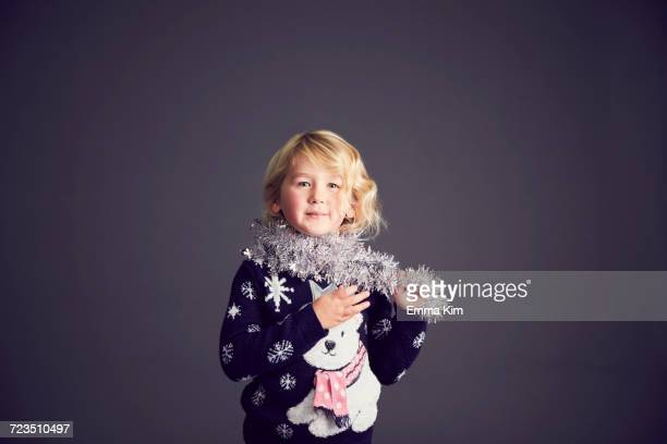 portrait of young girl wearing christmas jumper and tinsel around neck - christmas jumper fotografías e imágenes de stock