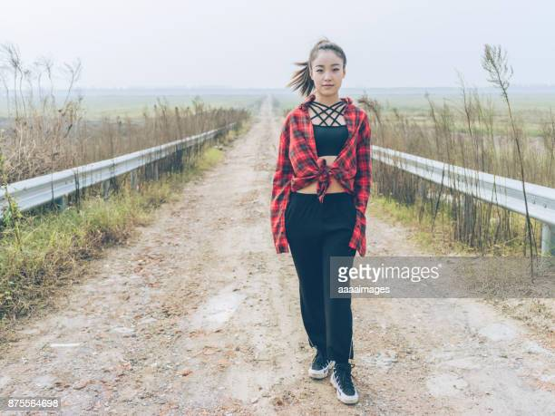 portrait of young girl wearing red plaid shirt standing at country road