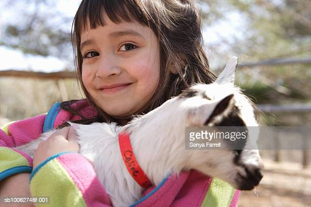 Portrait of young girl (4-5) with baby goat, smiling