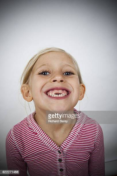 Portrait of young girl with gap in teeth pulling faces.