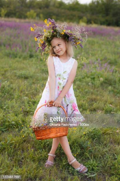 portrait of young girl with garland on head holding basket - garland stock pictures, royalty-free photos & images