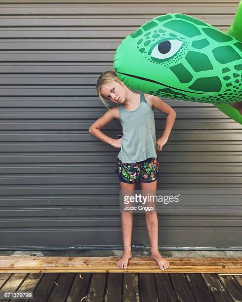 Portrait of young girl with giant inflatable turtl