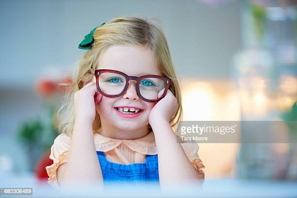 portrait of young girl with glasses looking to cam