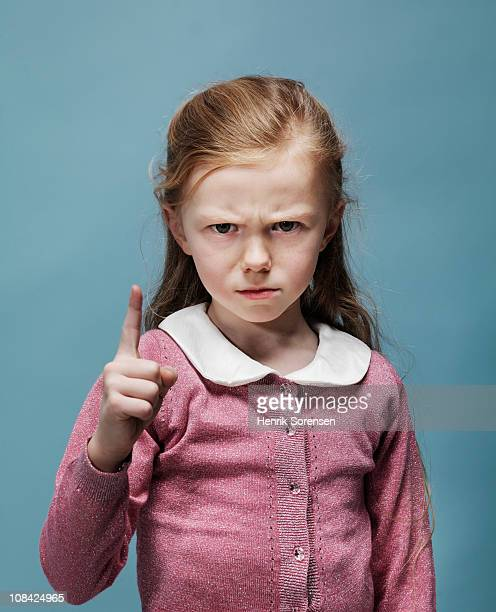 portrait of young girl with raised finger - scolding stock pictures, royalty-free photos & images