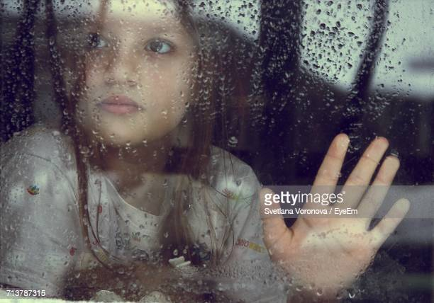Portrait Of Young Girl With Reflection On Window