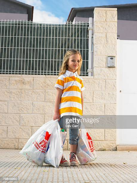 Portrait of young girl (4-6) with shopping bag, Alicante, Spain,