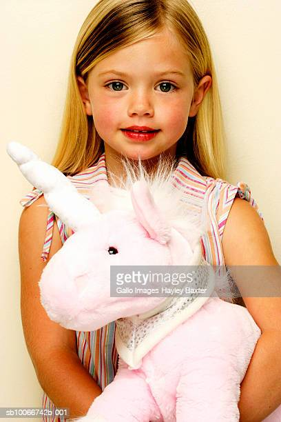Portrait of young girl (4-5) with stuffed unicorn