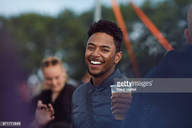 Portrait of young guy at festival holding beer