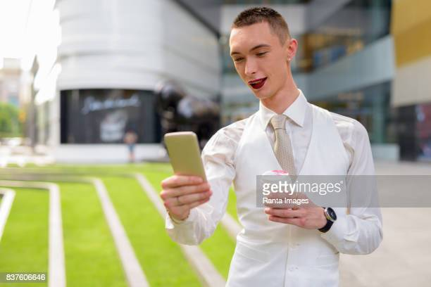 Portrait of young handsome androgynous businessman relaxing outside the building in Bangkok Thailand