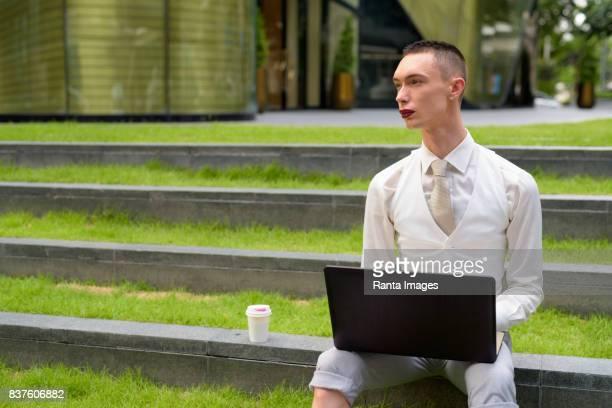 Porträt des jungen schönen androgynen Geschäftsmann entspannende außerhalb des Gebäudes in Bangkok Thailand