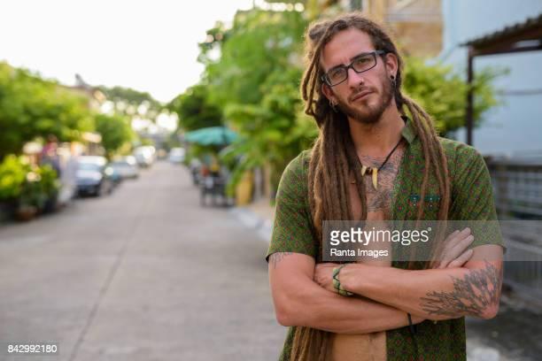 Retrato de joven guapo hispana turístico hombre con rastas, con camisa desabrochada en las calles al aire libre