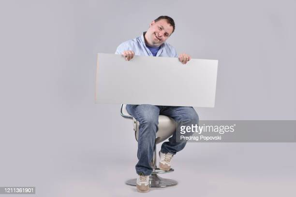 portrait of young happy man with down syndrome holding blank sign , human rights concept - person holding blank sign stock pictures, royalty-free photos & images