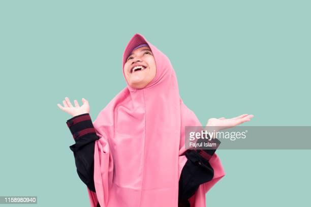 portrait of young happy muslim woman raising her arms in front of light blue background - alleen tieners stockfoto's en -beelden