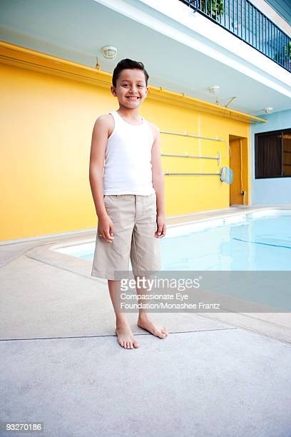 Portrait of Young Hispanic Boy by swimming pool.