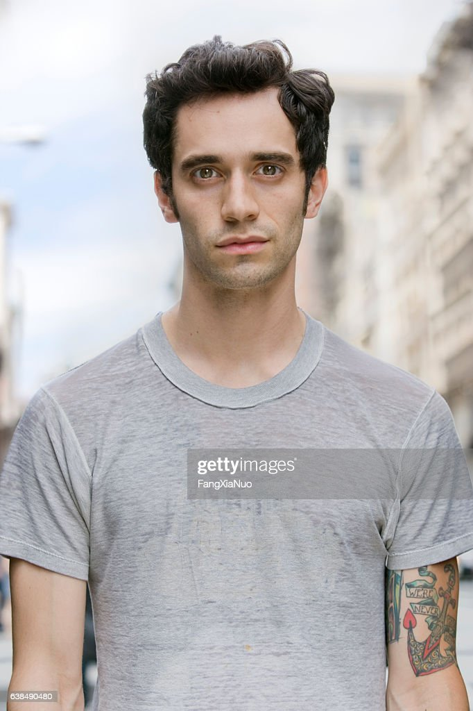 Portrait of young Hispanic man in downtown city : Stock Photo