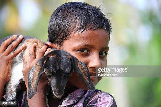 Portrait of young indian boy holding his baby goat in Alleppey on December 29, 2009 in Alapuzha near Trivandrum, Kerala, India.