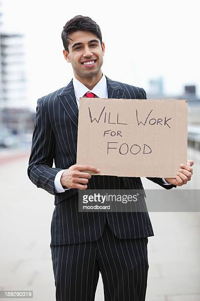 Portrait of young Indian businessman holding 'Will Work for Food' sign