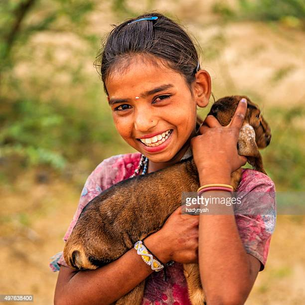 Portrait of young Indian girl holding goat, village near Jodhpur