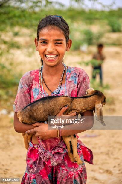 portrait of young indian girl holding goat, village near jodhpur - sari stock pictures, royalty-free photos & images