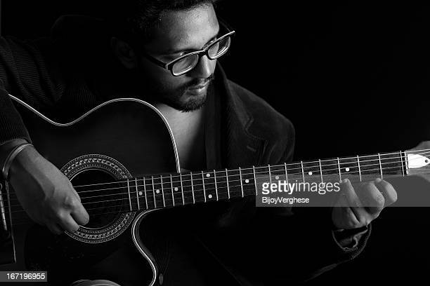 portrait of young indian man playing guitar - indian music stock photos and pictures