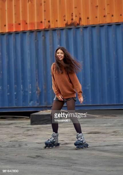 portrait of young inline-skater at industrial area - junge frau strumpfhose stock-fotos und bilder