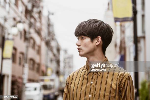 portrait of young japanese man wearing striped shirt - sideburn stock pictures, royalty-free photos & images