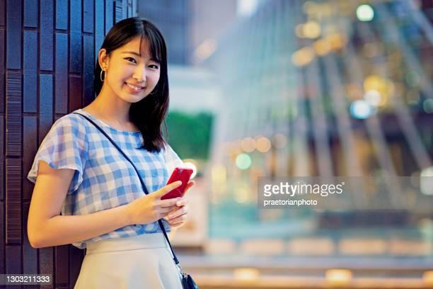 携帯電話を使った日本の若い女性の肖像 - waiting ストックフォトと画像