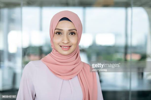 portrait of young malaysian woman in office - malay hijab stock photos and pictures