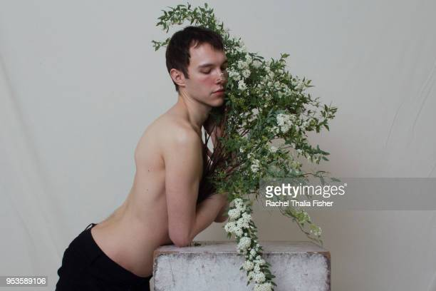 portrait of young male adult with bouquet of flowers - desire stock pictures, royalty-free photos & images