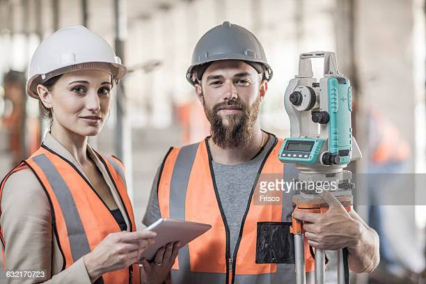 Portrait of young male and female surveyors on construction site