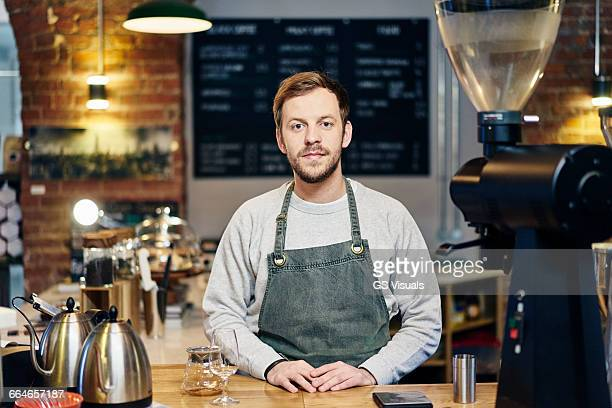 Portrait of young male barista at coffee shop kitchen counter