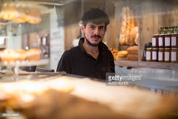 Portrait of young male barista behind cafe counter