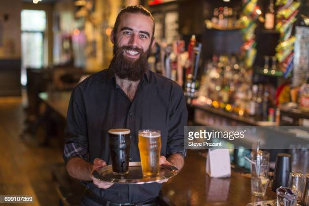 Portrait of young male bartender carrying tray of beer in public house