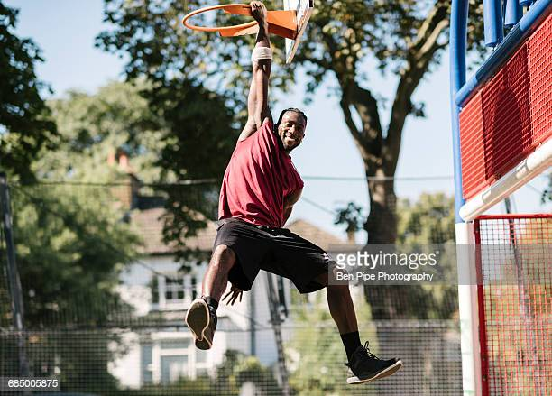 portrait of young male basketball player hanging from basketball hoop - showing off stock photos and pictures