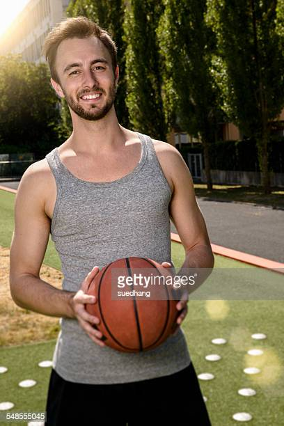 Portrait of young male basketball player on sports field