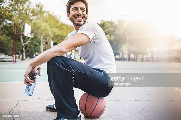 Portrait of young male basketball sitting on ball