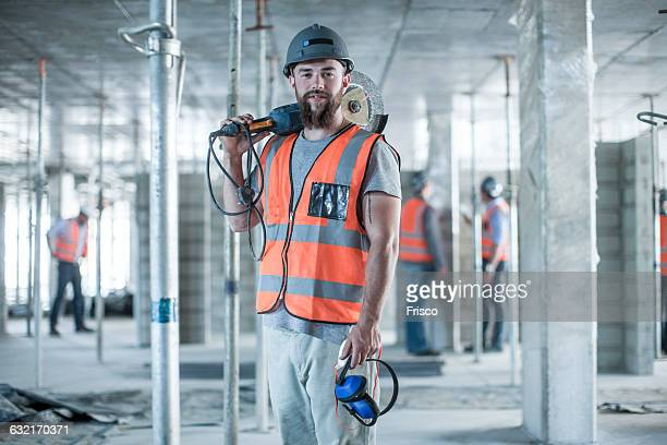 Portrait of young male builder carrying circular saw on shoulder on construction site