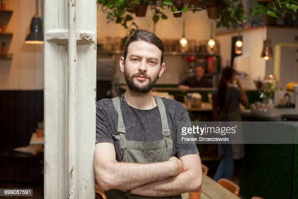 Portrait of young male cafe owner in cafe