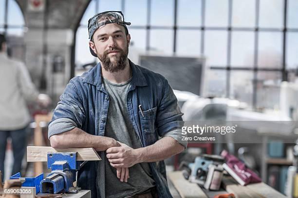 portrait of young male carpenter in antique restoration workshop - schreiner stock-fotos und bilder