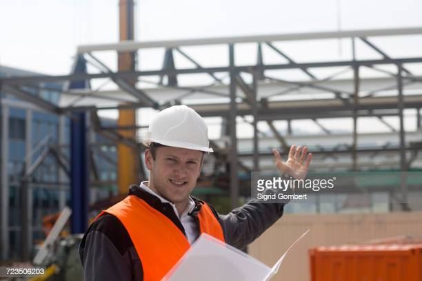 Portrait of young male civil engineer showing construction frame on construction site