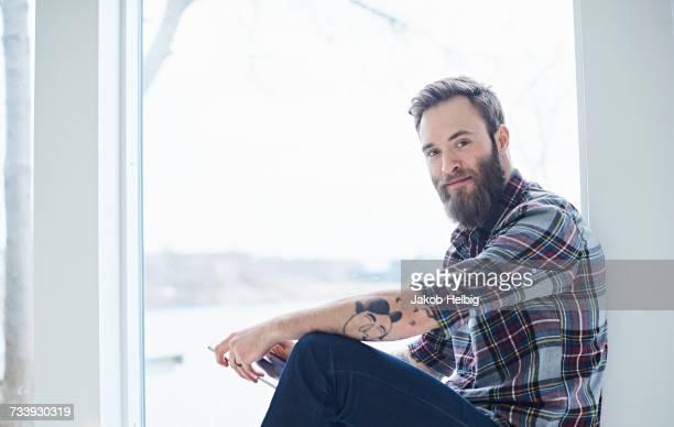 Portrait of young male designer in design studio window seat