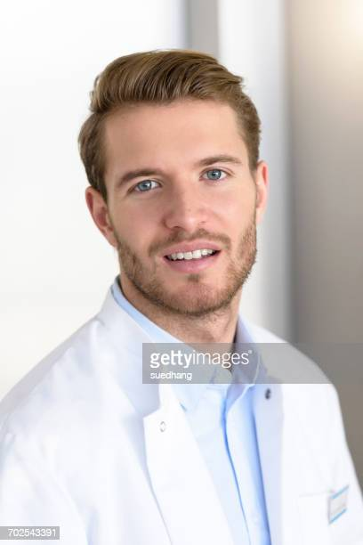 portrait of young male doctor in hospital - junior doctor stock pictures, royalty-free photos & images