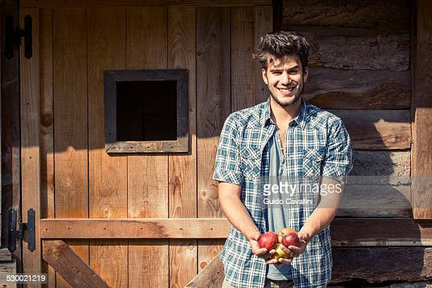 Portrait of young male farmer holding apples, Premosello, Verbania, Piemonte, Italy
