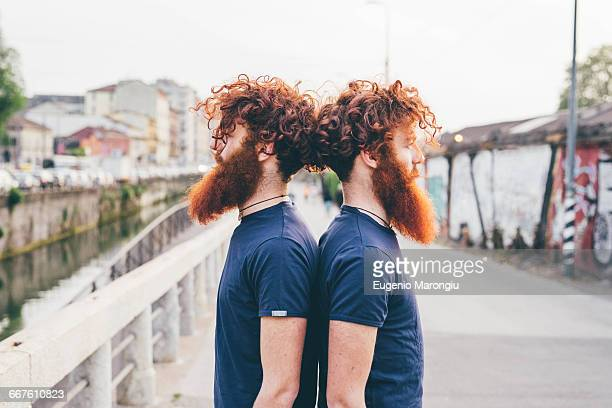Portrait of young male hipster twins with red hair and beards back to back on bridge