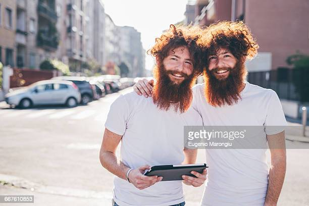 portrait of young male hipster twins with red hair and beards on city street - identical twin stock pictures, royalty-free photos & images