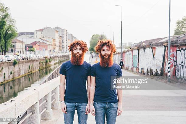 portrait of young male hipster twins with red hair and beards standing on bridge - identical twin stock pictures, royalty-free photos & images