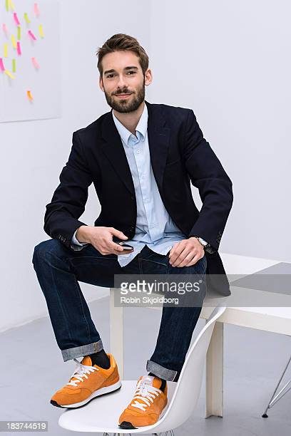 portrait of young male in design studio - sitting foto e immagini stock