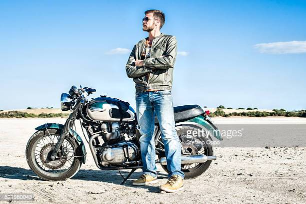 Portrait of young male motorcyclist on arid plain, Cagliari, Sardinia, Italy
