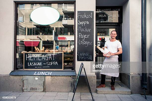 portrait of young male owner holding bread loafs while standing outside bakery - facade stock pictures, royalty-free photos & images
